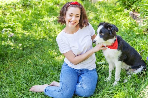Giovane donna che gioca con un simpatico cucciolo di cane border collie nel giardino estivo o nel parco cittadino all'aperto