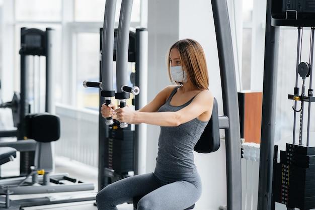 La giovane donna fa sport in maschera durante la pandemia