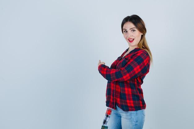 Giovane donna che punta indietro in camicia a quadri e sembra sorpresa. vista frontale.