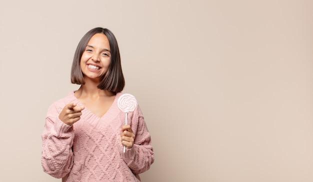 Giovane donna che punta alla telecamera con un sorriso soddisfatto, fiducioso, amichevole, scegliendo te