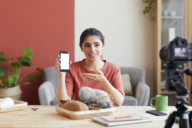 Giovane donna che indica al telefono cellulare alla sua mano e dice di seguire del suo blog che esegue blog di ricamo