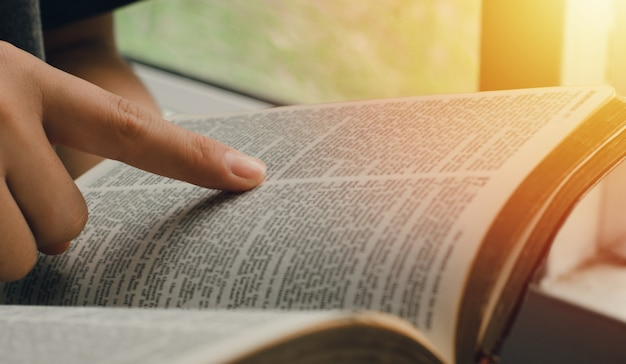 Una giovane donna che indica i versetti delle scritture che sono veritieri. mentre leggevo la bibbia al mattino vicino al davanzale della finestra