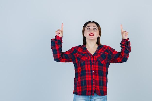 Giovane donna rivolta verso l'alto, guardando verso l'alto in camicia a quadri e guardando grato, vista frontale.