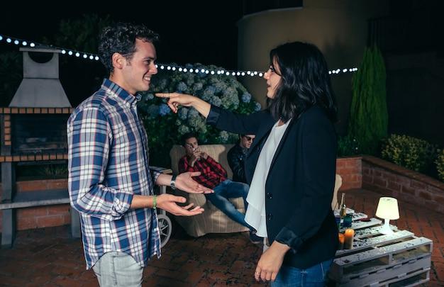 Giovane donna che indica con il dito l'uomo sorridente in una festa all'aperto con i loro amici. concetto di amicizia e celebrazioni.