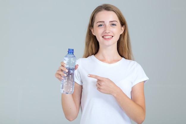 La giovane donna indica una bottiglia di acqua in sua mano, isolata su gray