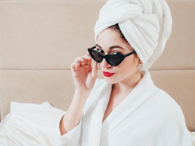 Ritratto di giovane donna. cura, tempo libero e tempo di relax. donna in accappatoio e turbante che dà una occhiata sopra gli occhiali da sole.