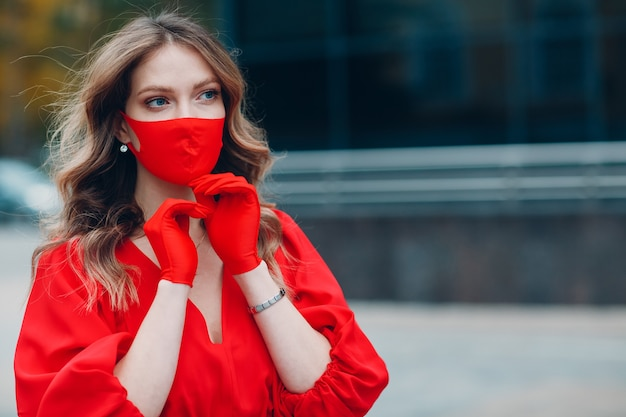 Il ritratto della giovane donna in vestito e guanti rossi mette sulla mascherina medica alla via fuori