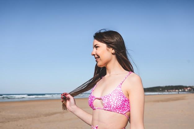 Ritratto di giovane donna con un bikini rosa sulla spiaggia