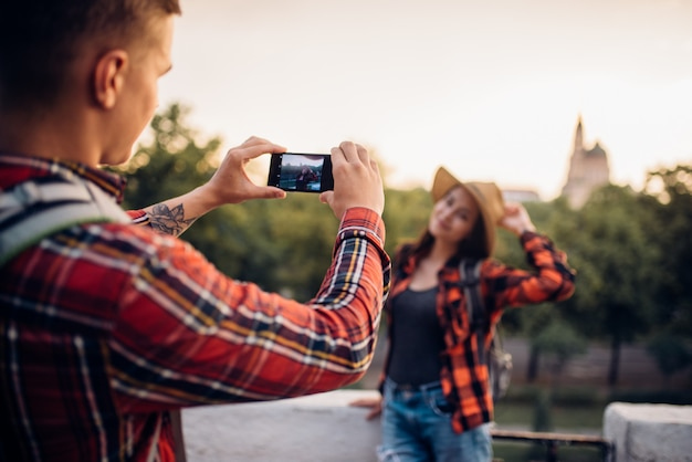 La giovane donna posa sull'escursione nella città turistica. escursioni estive di coppia amore. escursione all'avventura di un giovane uomo e una donna