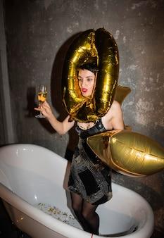 Giovane donna in posa nella vasca da bagno a casa
