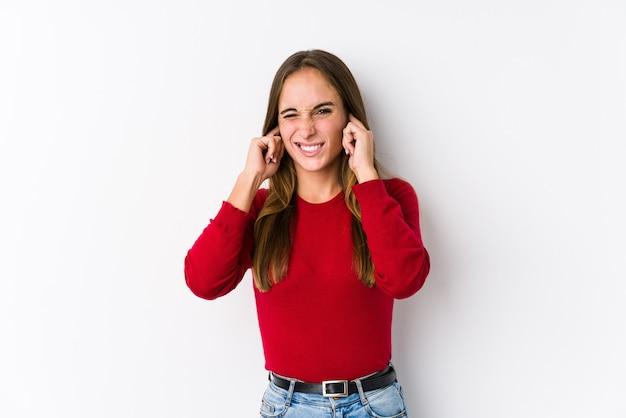 Giovane donna in posa isolato che copre le orecchie con le mani
