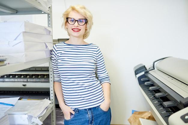 Giovane donna che propone nella tipografia