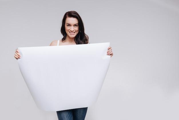 Giovane donna in posa mentre mostra un grande foglio di carta bianco