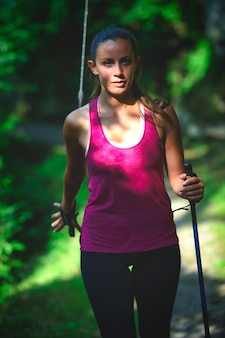 Una giovane donna pratica il nordic walking