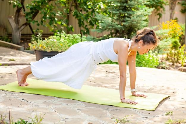 Giovane donna pratica yoga in giardino