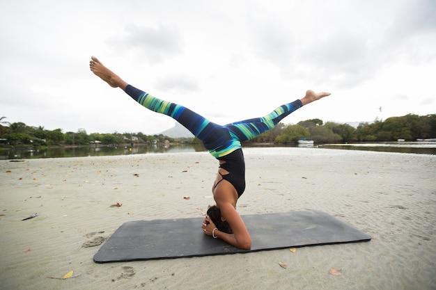 Giovane donna pratica yoga sulle rive dell'oceano indiano a mauritius
