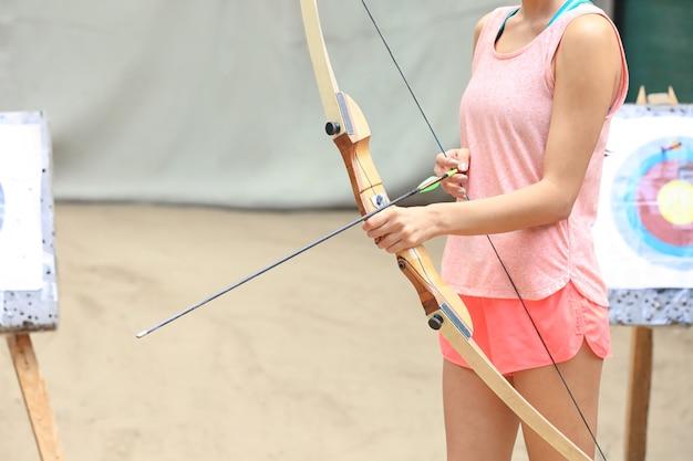 Giovane donna che pratica tiro con l'arco all'aperto