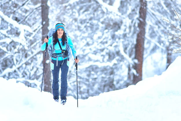 Giovane donna pratica dello sci alpinismo durante una nevicata nel bosco