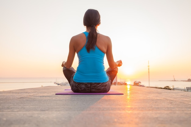Giovane donna a praticare yoga sulla spiaggia.