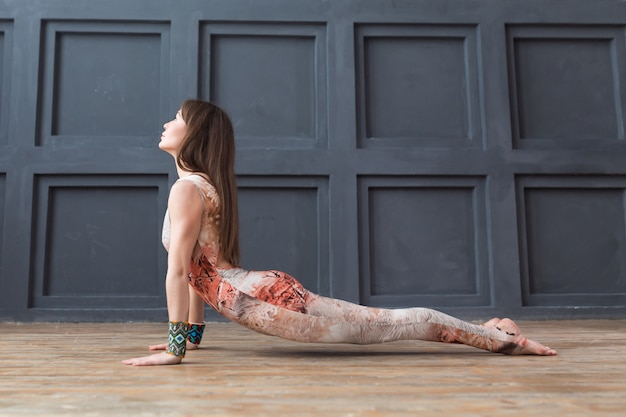 Posa di pratica della cobra di yoga della giovane donna