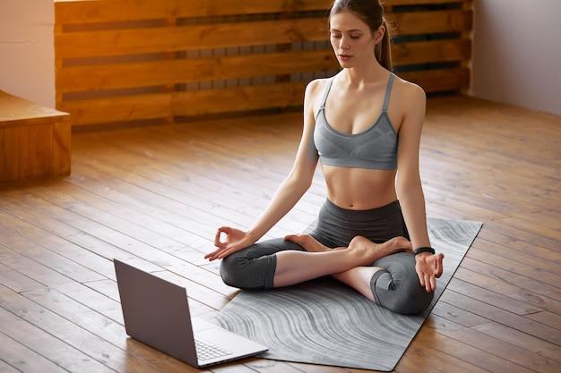 Giovane donna a praticare yoga a casa