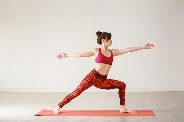 Giovane donna che pratica yoga su studio di luce al chiuso