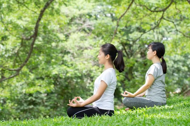 Giovane donna che pratica lo yoga nella natura, donna asiatica sta praticando lo yoga nel parco cittadino