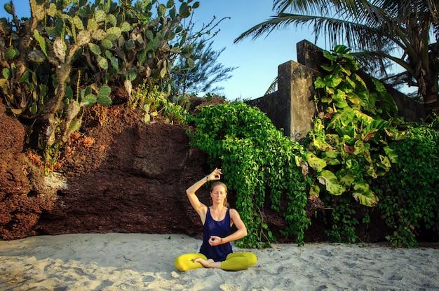 Yoga di pratica della giovane donna sopra all'aperto
