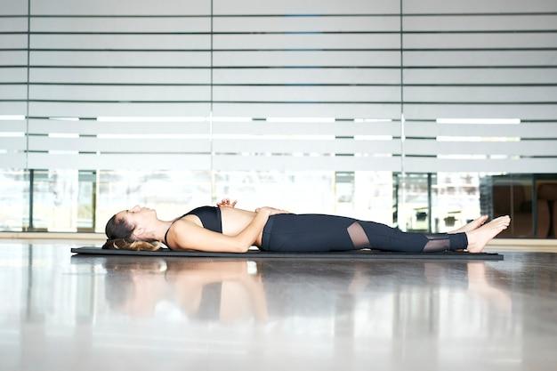 Giovane donna a praticare yoga o pilates in una palestra, esercizio in abbigliamento sportivo, facendo posa cadavere.