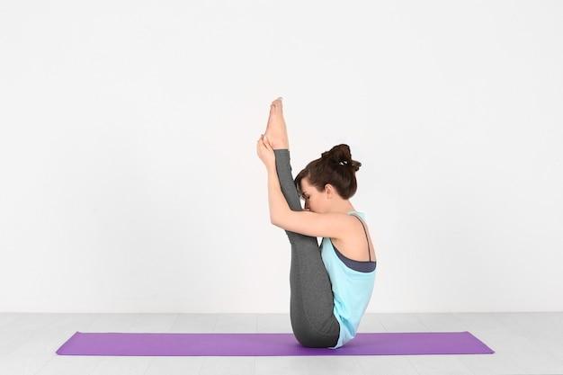 Yoga di pratica della giovane donna su bianco