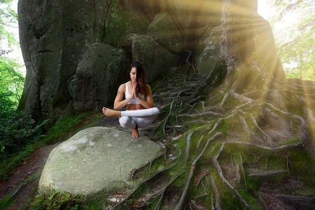 Yoga praticante della giovane donna all'aperto