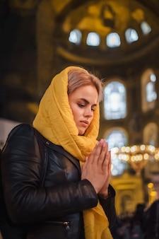 Giovane donna che prega e sentire armonia, amore nel cuore