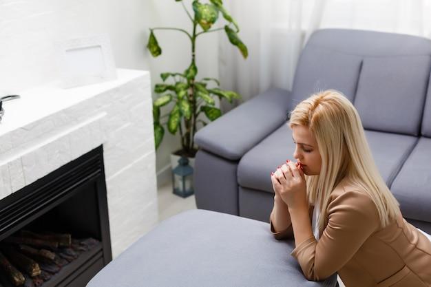 La giovane donna prega a casa