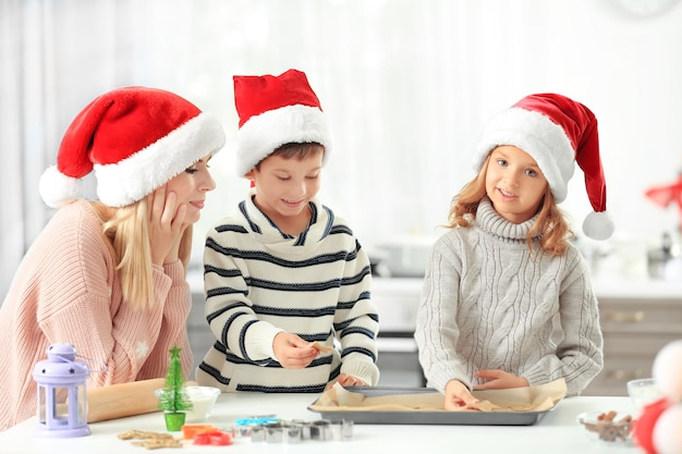Giovane donna che prepara i biscotti di natale con i bambini piccoli in cucina