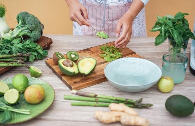 Giovane donna che prepara il succo della disintossicazione - ragazza che produce frullato con la verdura e la frutta verdi