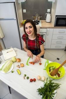 Giovane donna che prepara la cena in cucina. uno stile di vita sano.