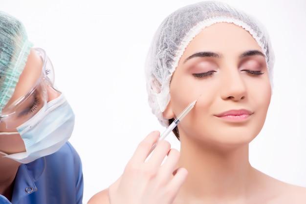 Giovane donna che prepara per la chirurgia plastica isolata su bianco