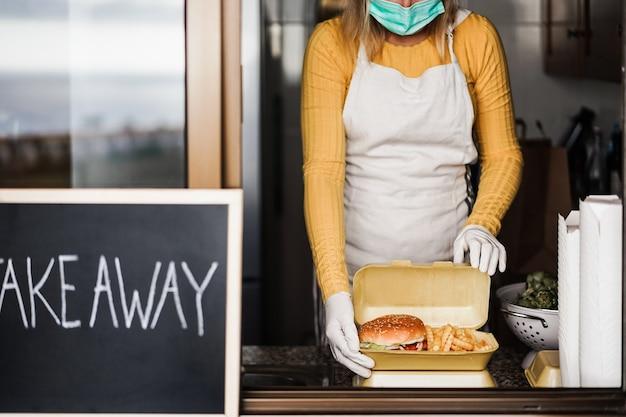 Giovane donna che prepara fast food da asporto all'interno del ristorante della cucina - focus sulle mani che tengono l'hamburger