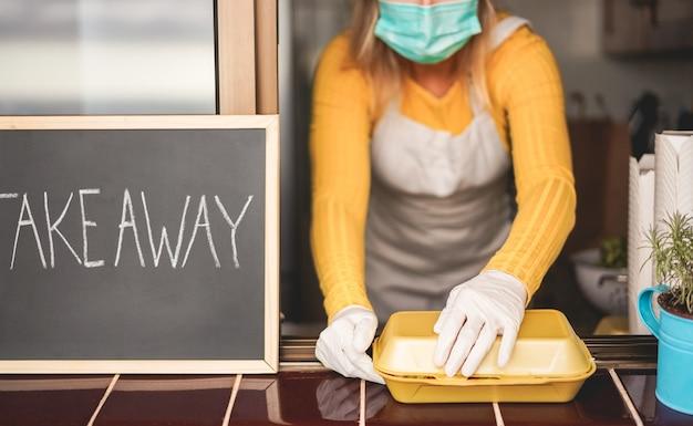 Giovane donna che prepara cibo da asporto all'interno del ristorante durante il periodo di epidemia di coronavirus