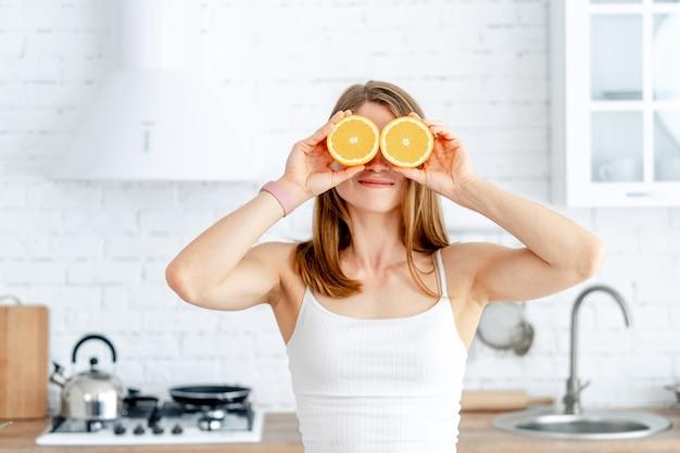 Giovane donna che prepara gustosa limonata in cucina