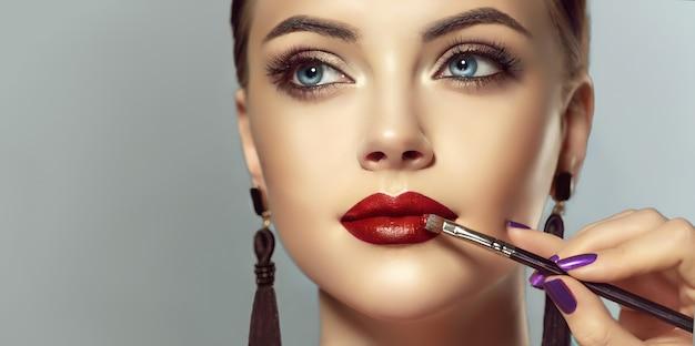 Modello grazioso della giovane donna sta dimostrando un trucco e una manicure nei colori rosso e nero