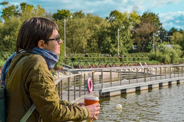 Giovane donna di profilo con una tazza di caffè si trova sul molo del laghetto cittadino e guarda l'acqua