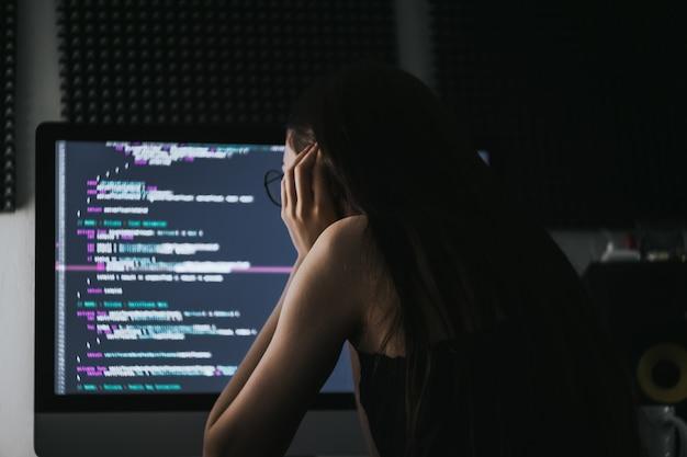 Il programmatore della giovane donna scrive il codice del programma sul computer