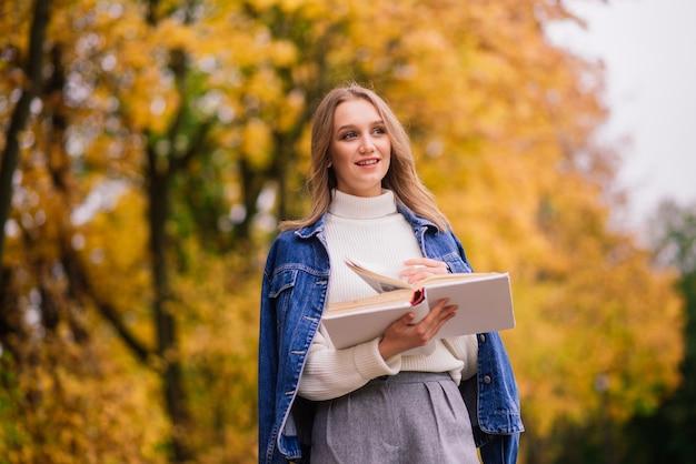 Giovane donna che protegge dal virus corona quando si cammina nel parco. sfondo autunnale.