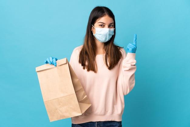 Giovane donna che protegge dal coronavirus con una maschera e in possesso di un sacchetto della spesa isolato sul muro blu che indica una grande idea