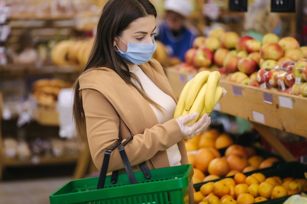 Giovane donna in guanti protettivi e maschera facciale tenere in mano bellissime banane fresche. bella ragazza con cesto di cibo scegliendo cibo in stand con frutta. shopping durante la quarantena. covid-19