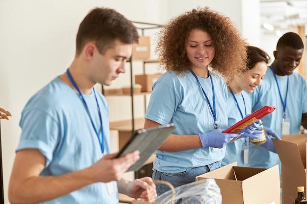 Giovane donna in guanti protettivi che smistano gli alimenti di imballaggio in scatole di cartone che fanno volontariato insieme