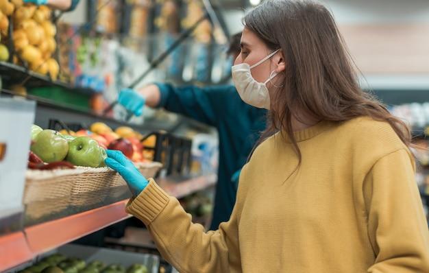 Giovane donna in una maschera protettiva acquista le mele