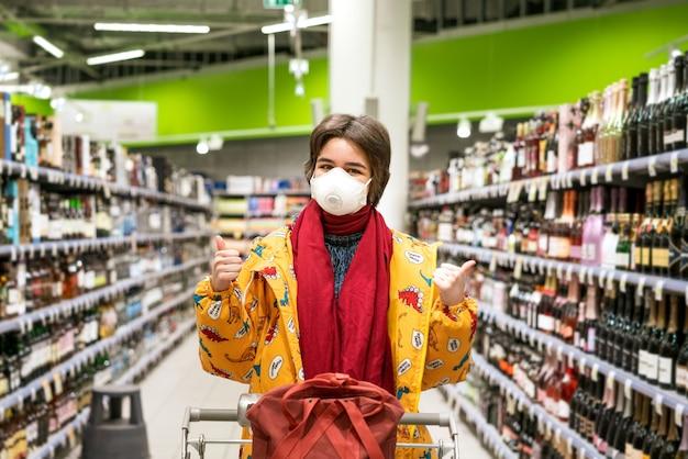La giovane donna in una maschera protettiva sceglie l'alcool in un supermercato, le scorte sono messe in quarantena