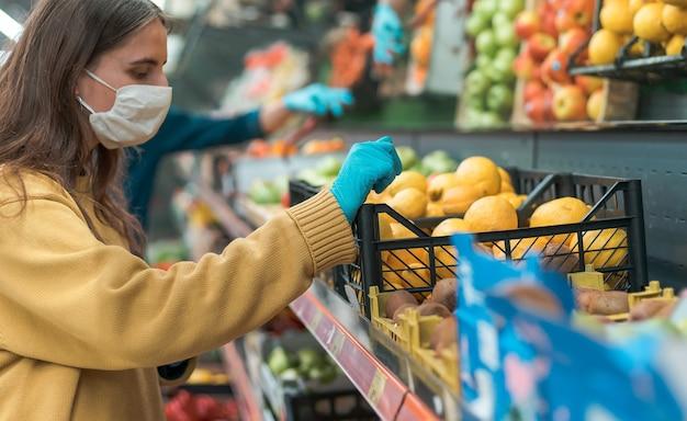 Giovane donna in una maschera protettiva scegliendo i limoni in un negozio.